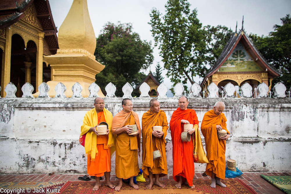 "11 MARCH 2013 - LUANG PRABANG, LAOS: Visiting Buddhist monks wait for Lao monks to pass them during the tak bat in Luang Prabang. The ""Tak Bat"" is a daily ritual in most of Laos (and other Theravada Buddhist countries like Thailand and Cambodia). Monks leave their temples at dawn and walk silently through the streets and people put rice and other foodstuffs into their alms bowls. Luang Prabang, in northern Laos, is particularly well known for the morning ""tak bat"" because of the large number temples and monks in the city. Most mornings hundreds of monks go out to collect alms from people.     PHOTO BY JACK KURTZ"