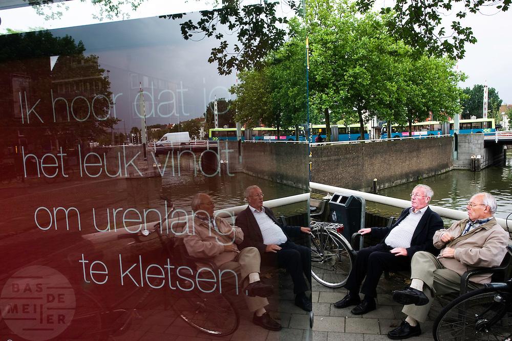 """Twee oudere mannen zitten op een bankje te praten met tegenover hun een reclame van Ziggo met de tekst """"Ik hoor dat je het leuk vindt om urenlang te kletsen"""""""