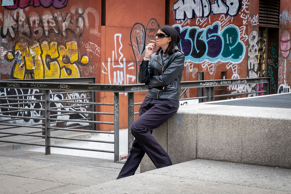 A woman wearing a black leather jacket and dark sunglasses sits smoking a cigarette on the 30th of October 2019 in front of a building covered in graffiti in Plaza de Juan Goytisolo, central Madrid, Spain. (photo by Andrew Aitchison / In pictures via Getty Images)