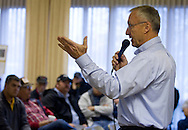 Hertz Real Estate Services real estate agent and auctioneer Marv Huntrods motions to the crowd as people bid during a farm auction at the Eagle Grove Masonic Lodge in Eagle Grove, Iowa on Thursday, October 18, 2012.