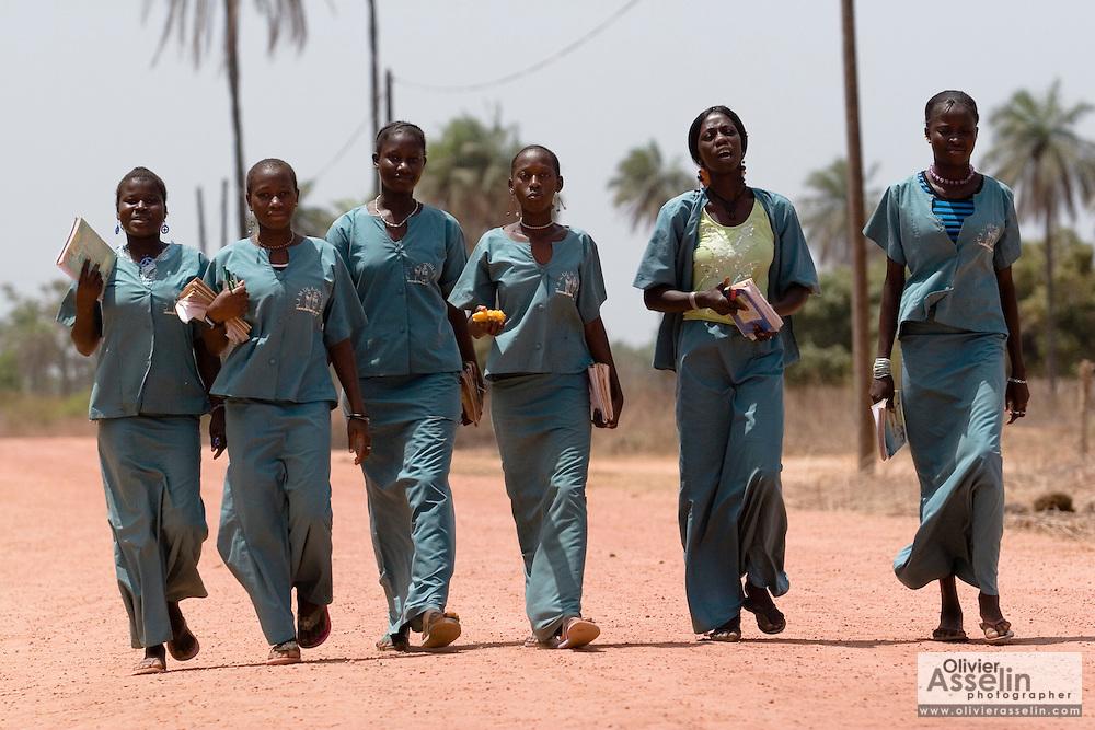 A group of girls in school uniforms walk back from school near the village of Kabiline, Senegal on Wednesday June 13, 2007.....