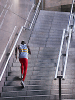 Male athlete running up staircase outside building