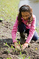 girl in pink planting in a garden