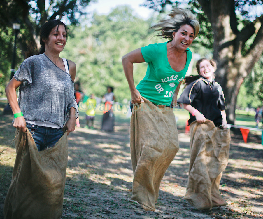 19 October 2014. New Orleans, Louisiana. <br /> Sack racing ladies at the New Orleans' Irish Network's third Family Day event with fun and games for kids and adults alike. With Irish dancing, egg and spoon and sack races with a good old fashioned tug of war to round things off.<br /> Photo; Charlie Varley/varleypix.com