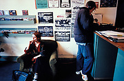 A woman sits looking bored as her boyfriend listens to vinyl in a record shop, 1998.