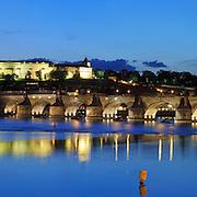 Skyline of Prague (Praha) at night overlooking the River Vltava toward the Charles Bridge and Prague Castle