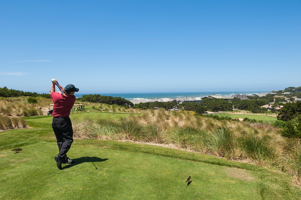 Head golf pro Mark Swift teeing off at hole #15 on the course at Salishan Spa & Golf Resort, central Oregon Coast..