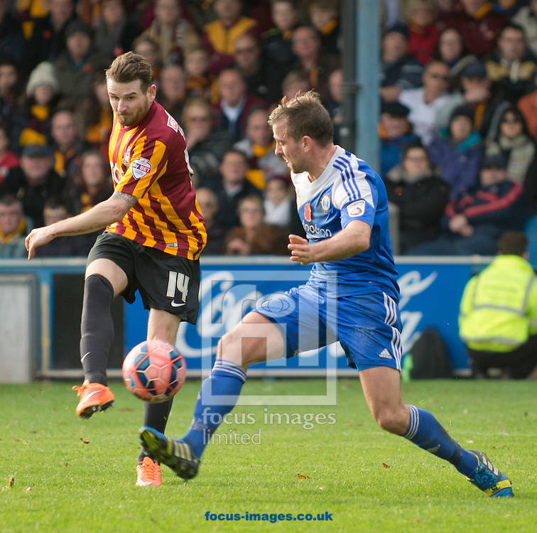Mark Yeates of Bradford City hits a shot at goal as Kevin Roberts of FC Halifax Town closes down during the The FA Cup match at Shay Stadium, Halifax<br /> Picture by Russell Hart/Focus Images Ltd 07791 688 420<br /> 09/11/2014