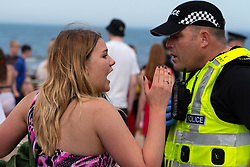 Edinburgh, Scotland, UK. 31 July, 2020. Temperature of 25C and sunshine brought huge crowds to Portobello Beach outside Edinburgh. Several large groups of teenagers were enjoying beach and alcoholic drinks were very popular. Pictured; At approx 3pm trouble broke out between young people on the the beach and police. Police reinforcements were quickly on scene and several people were apprehended. Westbank Street was closed to traffic and approx 30 police are patrolling the promenade. Police are confiscating alcohol from the teenagers remaining got the beach.  Iain Masterton/Alamy Live News