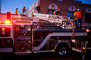 Fire fighters and officials finish inspecting damage from the rooftop of Donut Avenue in downtown Calexico, CA, April 7, 2010. The adjacent building had suffered significant parapet damage but the donut shop would remain open, albeit with a restriction on foot traffic near its damaged neighbor. A 7.2 magnitude earthquake in Baja California on Easter Sunday was felt as far away as Los Angeles.