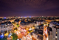Paris, View across the rooftops of the City lit up at night.