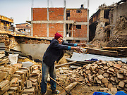 01 MARCH 2017 - KHOKANA, NEPAL: A man sets aside wood scavenged for firewood at the site of a building that was destroyed in the Nepal earthquake of 2015. Wood that can be reused for construction is set aside, but most rural Nepalis cook and heat their homes with firewood, and wood that can't be used in construction is used for firewood. Recovery seems to have barely begun nearly two years after the earthquake of 25 April 2015 that devastated Nepal. In some villages in the Kathmandu valley workers are working by hand to remove ruble and dig out destroyed buildings. About 9,000 people were killed and another 22,000 injured by the earthquake. The epicenter of the earthquake was east of the Gorka district.     PHOTO BY JACK KURTZ