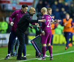 WIGAN, ENGLAND - Monday, February 19, 2018: Manchester City's manager Pep Guardiola speaks to David Silva during the FA Cup 5th Round match between Wigan Athletic FC and Manchester City FC at the DW Stadium. (Pic by David Rawcliffe/Propaganda)