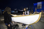 Diamond Campbell, student participated in building the boat, is showing her work to her family member, Tawaana Campbell and Nagele Johnson, Rocking the Boat, Hunts Point, Dec.13, by Qingqing Chen
