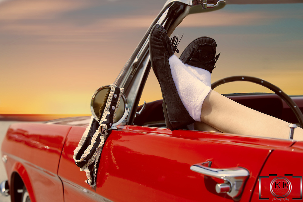 A young lady, with her feet draped over the door of a 1966 Mustang convertible, and her panties hanging from the side mirror.