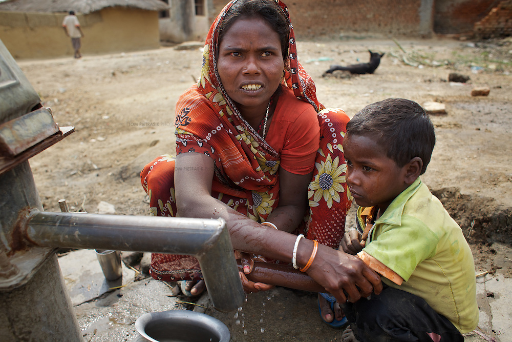 Kari Devi washes her son Pramod, 3, with one of the two, unreliable, hand pumps in Mananbigha village. <br /> <br /> Mananbigha resident and day-wage laborer, Congress Manjhi died of hunger in April 2010. He was a landless Maha Dalit (Bhuiyan caste). He had tuberculosis. Bedridden, he had been unable to work for four years. As a consequence, Congress' wife, Kari Devi, 35, became the sole breadwinner for their family of four children. When Kari Devi was bitten by a dog in 2010, she was not able to work for 15 days. She had to travel 40km for a rabies vaccination as the local hospital in Barachatti was out of stock. This incurred substantial expense at a time when no one in the family was bringing in an income. Kari Devi had to borrow money for treatment. The family had not been granted a BPL (Below Poverty Line) card even thought they were entitled to one. As a consequence they had no access to rations from the PDS (Public Distribution System). With no food, Congress Manjhi eventually succumbed to tuberculosis. Following his death, it took representation from the Oxfam-supported Nyadal, a local village court, to force the administration into granting Kari Devi the 25kg of grains to which she and her family are entitled as part of the Antyodaya scheme (providing staple food for the poorest of the poor). Kari Devi must now bring up her four children alone. She is a member of the local five-person vigilance committee that reports to the Nyadal.<br /> <br /> Like much of rural Bihar state - particularly among low caste communities - the residents of Mananbigha regularly go hungry. Some have died as a result of food shortages. There is a scarcity of water in the area and no irrigation facility. Though there are schemes in place to support vulnerable families, it is an ongoing struggle for residents to claim benefits, including rations, that are by rights theirs. Oxfam partners have helped to promote awareness of social security schemes among residents in Mananbigha village and provided them the