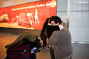 "Amid the hectic arrivals concourse of Heathrow airport's Terminal 5, two friends hold on to each other tight after an international arrival. Standing in front of a Mastercard ad which shows scenes of London, the coupe squeeze each other tight amid an otherwise hectic airport concourse in heathrow's Terminal 5. They have clearly missed each other after such a break apart but are otherwise oblivious to the crowds that surround them in this busy international airport. They embrace with genuine affection for each other in a display of sexual freedom that is otherwise seen as a taboo in other countries. From writer Alain de Botton's book project ""A Week at the Airport: A Heathrow Diary"" (2009)."