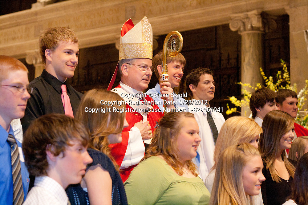 """Priest wearing red vestments surrounded by teenagers during confirmation Mass. Basilica of """"St Mary"""" St Paul Minnesota MN USA"""