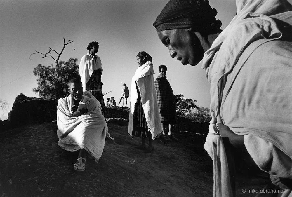 Pilgrims gather for morning prayers at the edge of Met Maryam one of the undergroung rock hewn churches of lalibela. Ethiopia