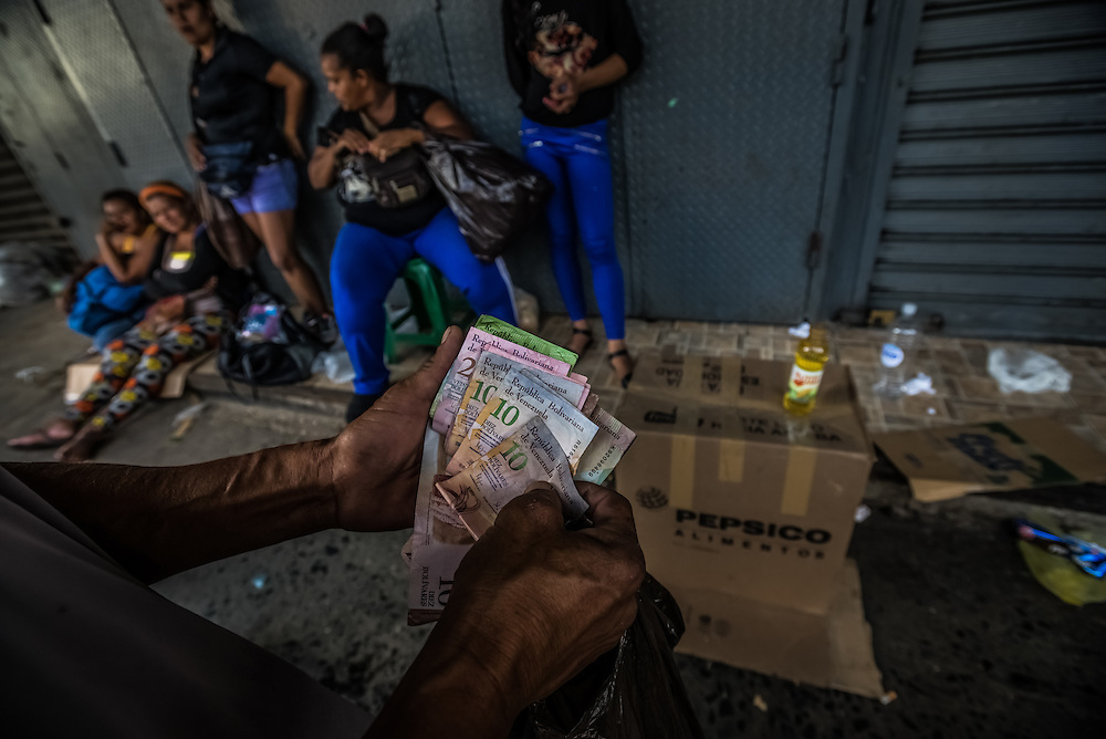 CARACAS, VENEZUELA - JANUARY 15, 2015: Vendors illegally sell blackmarket butter, soap and cooking oil outside of the Quinto Crespo government market for over five times the price of each item set by government price controls. Despite being a petro-state with one of the largest oil reserves in the world, basic food goods such as cooking oil, milk, chicken, coffee, rice, sugar and corn meal are difficult to find in stores across Venezuela. PHOTO: Meridith Kohut