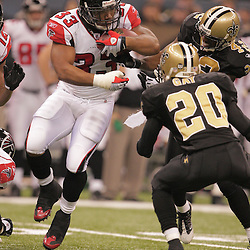 2008 December, 07: Atlanta Falcons running back Michael Turner (33) runs as Saints defenders Randall Gay (20) and Jason David (42) close in for a tackle during a 29-25 victory by the New Orleans Saints over NFC South divisional rivals the Atlanta Falcons at the Louisiana Superdome in New Orleans, LA.