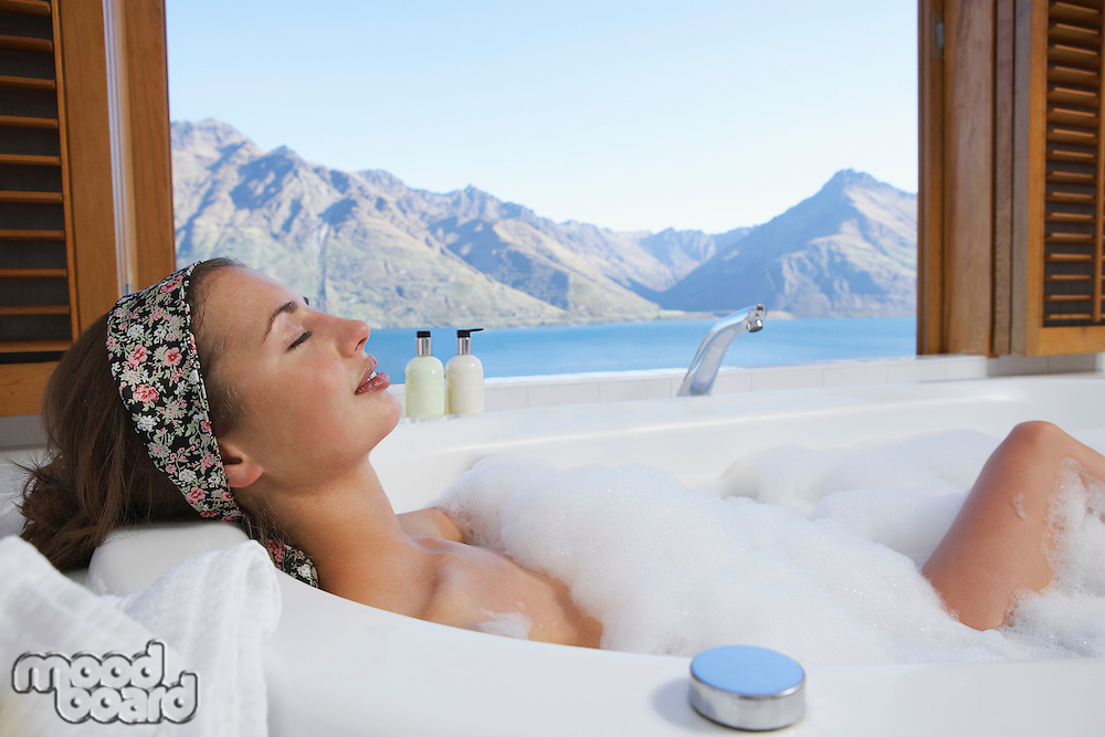 Woman taking a bubble bath with mountain lake outside window