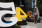 A city worker smokes a cigarette as a woman drinks water next to an art installation entitled 'One Through Zero (The Ten Numbers)' by American pop artist Robert Indiana (b 1928), in Lime Street, City of London, the capital's Square Mile, and its financial heart. Situated in the capital's Square Mile, its financial heart, are surrounding offices and corporate headquarters from the finance and insurance sector, most notably being the nearby Lloyds of London building. This series of sculptures is composed of 10 brightly painted numerical digits, each made of aluminum and set on its own base. Their construction took place at the former Lippincott Foundry in North Haven, Connecticut from 1980 to 1983