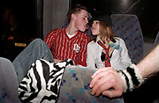 Two clubbers on a coach sticking their tongues out at each other, Passion, Emporium, Milton Keynes, UK, 2002