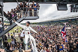 July 16, 2017 - Silverstone, United Kingdom - British driver LEWIS HAMILTON of Mercedes AMG Petronas sits atop a fence to take a selfie with the crowd after winning the Formula One British Grand Prix. (Credit Image: © Malte Christians/Hoch Zwei via ZUMA Wire)