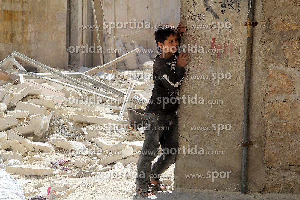 06.07.2015, Aleppo, SYR, B&uuml;rgerkrieg in Syrien, im Bild ein junger Syrer nachdenklich in der zerst&ouml;rten Stadt // A Syrian boy looks on as he stands next to the ruins of a destroyed building following a reported bomb barrel attack by Syrian government forces hit al-Mayser rebel held neighborhood, Syria on 2015/07/06. EXPA Pictures &copy; 2015, PhotoCredit: EXPA/ APAimages/ Ameer al-Halbi<br /> <br /> *****ATTENTION - for AUT, GER, SUI, ITA, POL, CRO, SRB only*****