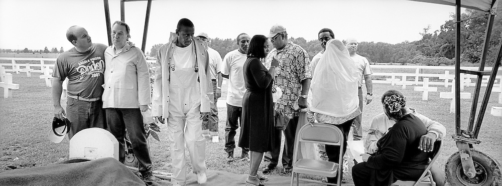 Calvin Dumas, second right, is consoled by a friend after the burial of Dumas' closest friend, George Alexander, at the Angola State Penitentiary cemetery. The Angola Prison hospice program is responsible for planning memorial services and funerals for its patients. These services allow for family members to grieve alongside the inmate's prison friends.