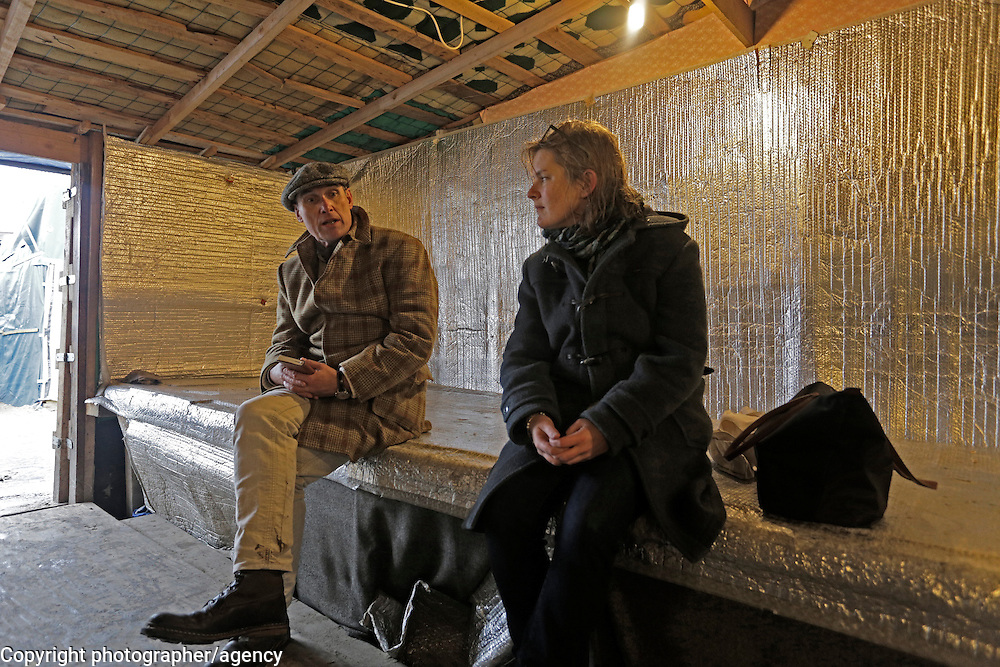 MSF doctor, Natalie Roberts (R) talks with Sunday Times writer AA Gill in the Jungle refugee camp restaurant 22 January 2016, Calais, France, 22 January 2016.