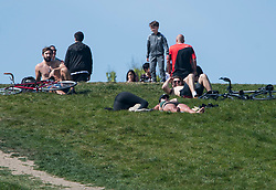 © Licensed to London News Pictures. 23/04/2020. London, UK. People sunbathing on Primrose Hill, north London during a pandemic outbreak of the Coronavirus COVID-19 disease. The public have been told they can only leave their homes when absolutely essential, in an attempt to fight the spread of coronavirus COVID-19 disease. Photo credit: Ben Cawthra/LNP. Photo credit: Ben Cawthra/LNP