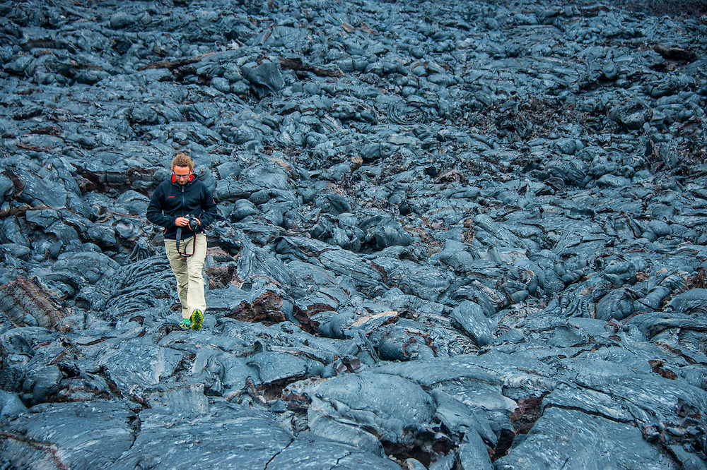 Man walking in cold lava field after an eruption of Tolbachik volcano, Kamchatka, Russia