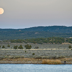 051611       Brian Leddy.A man fishes along the banks of Nutria Lake as the moon rises in Zuni on Monday evening. With the warm onset of warm weather, the fishing on area lakes should improve.