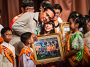 09 JANUARY 2016 - BANGKOK, THAILAND:      PRAYUTH CHAN-O-CHA, the Prime Minister of Thailand, listens to girl who presented him with a present during Children's Day festivities at Government House. National Children's Day falls on the second Saturday of the year. Thai government agencies sponsor child friendly events and the military usually opens army bases to children, who come to play on tanks and artillery pieces. This year Thai Prime Minister General Prayuth Chan-ocha, hosted several events at Government House, the Prime Minister's office.      PHOTO BY JACK KURTZ
