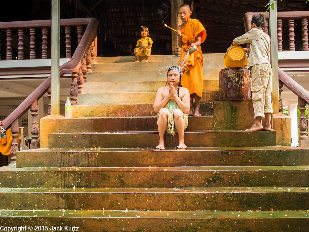 "14 MARCH 2105 - SIEM REAP, SIEM REAP, CAMBODIA: A Buddhist monk blesses a Cambodian woman at a monastery in the Angkor Thom part of the Angkor Wat complex. The area known as ""Angkor Wat"" is a sprawling collection of archeological ruins and temples. The area was developed by ancient Khmer (Cambodian) Kings starting as early as 1150 CE and renovated and expanded around 1180CE by Jayavarman VII. Angkor Wat is now considered the seventh wonder of the world and is Cambodia's most important tourist attraction.   PHOTO BY JACK KURTZ"