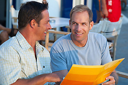 two men holding a menu and enjoying time together