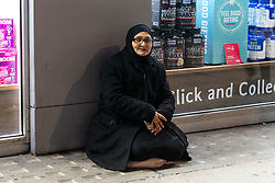 A woman begging on Oxford Street hides her cup as she realises she's being photographed. Homeless Britons are coming under increasing pressure as a surge of Roma beggars from Romania arrive on the streets of London to take advantage of the generosity of Christmas shoppers. London, December 04 2018.