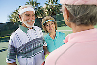 Three people on tennis court