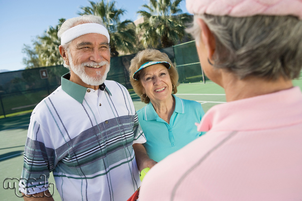 Three people on tennis court