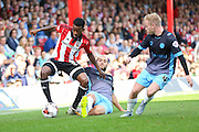 Brentford Midfielder Josh Clarke holds off a challenge from Sheffield Wednesday Forward Atdhe Nuhiu during the Sky Bet Championship match between Brentford and Sheffield Wednesday at Griffin Park, London, England on 26 September 2015. Photo by Phil Duncan.