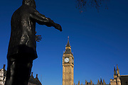 Reaching hands of ex-South African President Nelson Mandela's statue seemingly grasp Big Ben clock tower in Parliament Square..