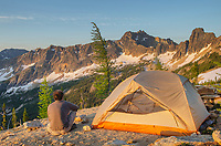 Adult male at daybreak sitting next to backpacking tent and gazing at view of Cutthroat Peak on ridge above Cutthroat Pass, near Pacific Crest trail. North Cascades Washington