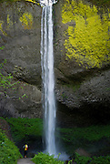Hiker pauses for dramatic view of 249foot plunge of Latourell Falls, Columbia Gorge, Oregon