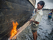 07 NOVEMBER 2014 - SITTWE, RAKHINE, MYANMAR: A worker applies tar, used as a water sealant, to a boat in the port of an IDP camp housing Rohingya Muslims near Sittwe. The boats were originally built as fishing boats but are increasingly being used by human traffickers to take people to Malaysia. The government of Myanmar has forced more than 140,000 Rohingya Muslims who used to live in Sittwe, Myanmar, into squalid Internal Displaced Person (IDP) camps. The forced relocation took place in 2012 after sectarian violence devastated Rohingya communities in Sittwe and left hundreds dead. None of the camps have electricity and some have been denied access to regular rations for nine months. Conditions for the Rohingya in the camps have fueled an exodus of Rohingya refugees to Malaysia and Thailand. Tens of thousands have put to sea in rickety boats hoping to land in Malaysia but sometimes landing in Thailand. The exodus has fueled the boat building boom on the waterfront near the camps. Authorities expect the pace of refugees fleeing Myanmar to accelerate during the cool season, December through February, when there are fewer storms in the Andaman Sea and Bay of Bengal.   PHOTO BY JACK KURTZ