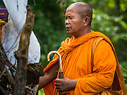 20 JUNE 2016 - DON KHONE, CHAMPASAK, LAOS:A Buddhist monk says a final prayer before lighting the funeral pyre of a man near Don Khone village on Don Khone Island. Don Khone Island, one of the larger islands in the 4,000 Islands chain on the Mekong River in southern Laos. The island has become a backpacker hot spot, there are lots of guest houses and small restaurants on the north end of the island. In the southern Lao funeral tradition, the deceased is cremated at the place of his choosing, usually a place he (or she) was especially fond of. In this case, the man chose to be cremated in a small clearing in the jungle a few kilometers from his home.      PHOTO BY JACK KURTZ