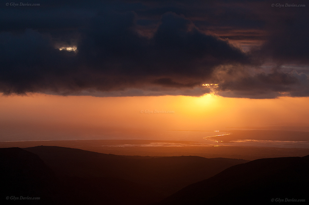Anglesey and it's most popular sandy beach, Llanddwyn in the sunset as seen fro the summit of Snowdon, (Yr Wyddfa) Wales' highest mountain.