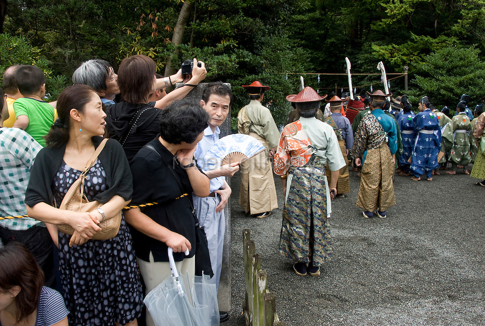 Visitors watch on as shrine priests pray during the annual Reitaisai Grand Festival at Tsurugaoka Hachimangu Shrine in Kamakura, Japan on  14 Sept. 2012.  Sept 14 marks the first day of the 3-day Reitaisai festival, which starts early in the morning when shrine priests and officials perform a purification ritual in the ocean during a rite known as hamaorisai and limaxes with a display of yabusame horseback archery. Photographer: Robert Gilhooly