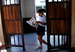 """A waitress at """"Bar San Juan"""" in central Havana, takes a break and reads a local newspaper. (Photo © Jock Fistick)"""
